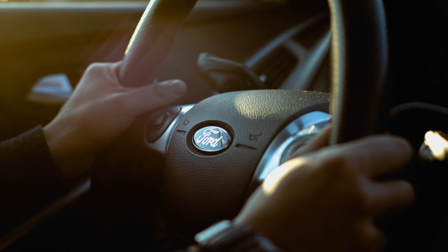 Man holding a Ford steering wheel